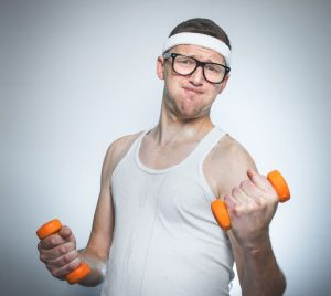 Funny tense man tries to lift a weight - dumbbells his biceps - muscle, isoalted on gray white. Nerd male exercise- doing fitness Keywords: funny;Sport;man;tense;lift;lifting;fitness;exercise;exercising;bodybuilding;biceps;muscle;push;tough;training;workout;tries;sportsman;undershirt;loony;fool;nerd;Expression;facial expression;small;dumbbells;isolated;gray;gray background;white;studio-shot;studio;close-up;closeup;weight;human;one;person;adult;young;strength