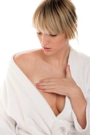 Woman applying cream on chest